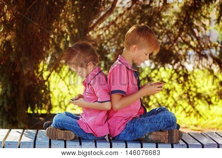 Two little boys playing games on mobile phone in sunny day sitting back to back