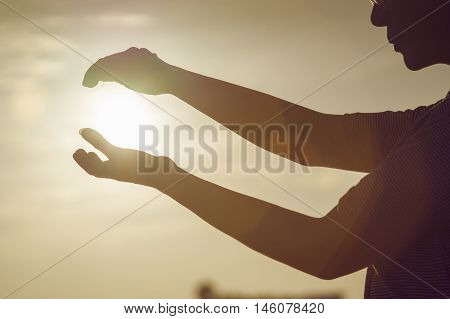 young woman use two hands to holding a sun on sunset moment,hoping concept,fighting,big think concept