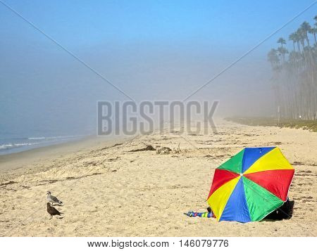 Brightly colored umbrella on the beach in the fog