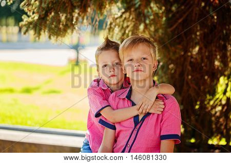 Two adorable sibling boys hugging and having fun outdoors. Brother love.