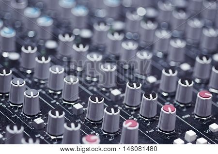 Closeup mixing faders and knobs as seen from above side angle, artistic studio equipment concept.