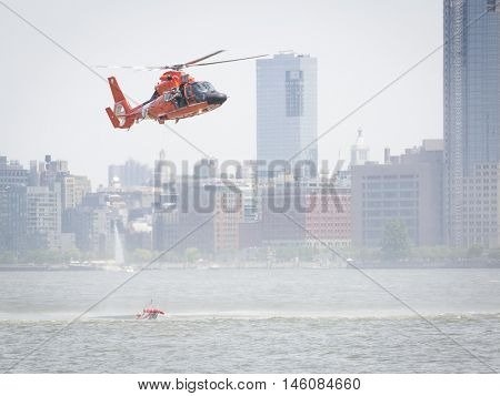 JERSEY CITY NJ MAY 29 2016: A rescue basket is lowered from the orange U.S. Coast Guard MH-65 Dolphin helicopter during a Search and Rescue demonstration at Liberty State Park during Fleet Week 2016.