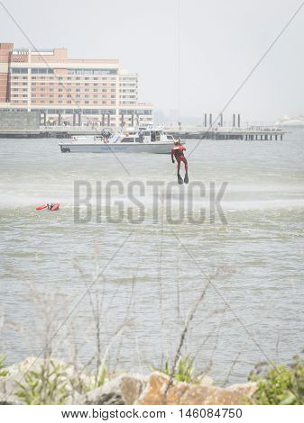 JERSEY CITY NJ MAY 29 2016: A U.S. Coast Guard rescue swimmer is hoisted by line into a USCG MH-65 Dolphin helicopter hovering above during a Search and Rescue demonstration for Fleet Week 2016.
