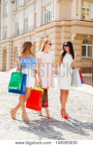 Three Happy Girlfriends Walking With Paperbags After Shopping