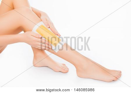 Close Up Of Woman Using Beeswax Stripe To Shave Her Leg