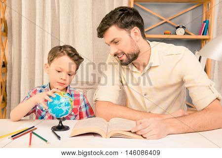 Little boy studing geography with his dad at home