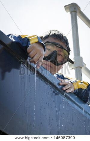 JERSEY CITY NJ MAY 29 2016: A US Navy EOD technician peeks out from the top of the glass of the 6,800 gallon mobile dive tank during Fleet Week NY 2016 in Liberty State Park.