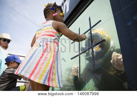 JERSEY CITY NJ MAY 29 2016: An unidentified little girl plays tic tac toe with a US Navy EOD technician on the glass of a 6,800 gallon mobile dive tank during Fleet Week NY 2016 in Liberty State Park.