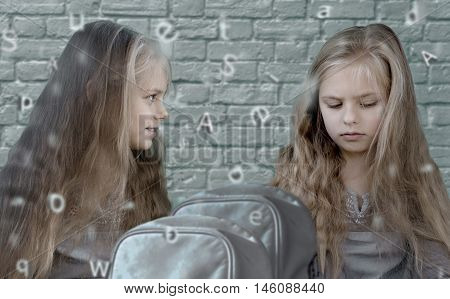 Two cute twins girls on the background of a brick wall with the alphabet