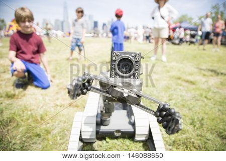 JERSEY CITY NJ MAY 29 2016: People watch a small unmanned ground vehicle the US Navy uses to locate and dispose of explosive devices during a demonstration in Liberty State Park for Fleet Week 2016.