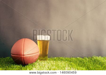 Vintage football and beer glass over grass