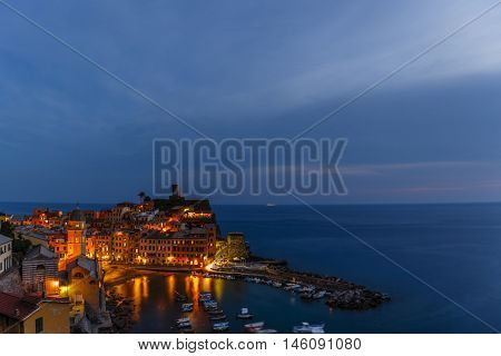 Night view from hill of Vernazza houses with lit light and blue sea, one of Cinque Terre villages , Liguria, Italy