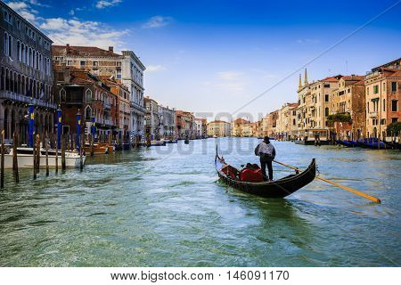 Gondolier sailing a gondola and view of the Grand Canal, Venice, Italy