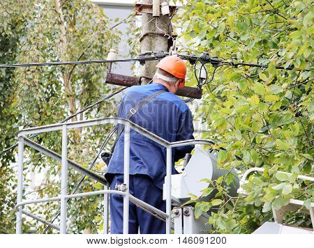Electrical worker repairing the wires on the pole with the help of the lift car