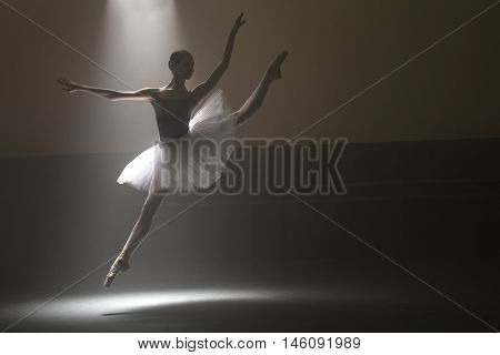 Incomparable ballerina making a jump in a dance hall. She is wearing the leotard with white tutu. Light falls from above behind her. Shoot in a low key. Horizontal.