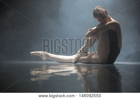 Young ballerina sitting on the floor in the dance hall. She clasps her hands one leg while the other leg is stretched forward. She is reflected on the floor surface. Smoke curled behind her. Light falls from above. Low key photo.