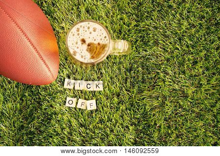 Vintage football over grass and beer jar with Kick Off message in tiles