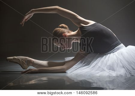 Pretty ballerina in the white tutu stretching her hands to the right while sitting on the splits in the dance hall. She is reflected on the floor surface. Light falls on her body from above. Low key photo.
