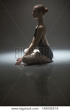 Pacified ballerina sitting in the lotus position on the floor in the dark dance hall. She is wearing the black leotard with pointe shoes. She is reflected on the floor surface. Low key photo. Vertical.