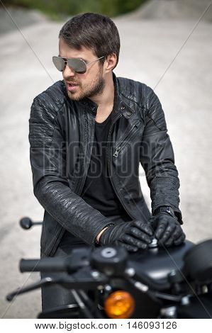 Handsome man with a beard on the black motorcycle on the blurry background outdoors. His hands lies on the motorcycle. He looks to the left. He wears black jeans, a black T-shirt, black moto gloves, a black leather jacket and sunglasses. He has a bracelet