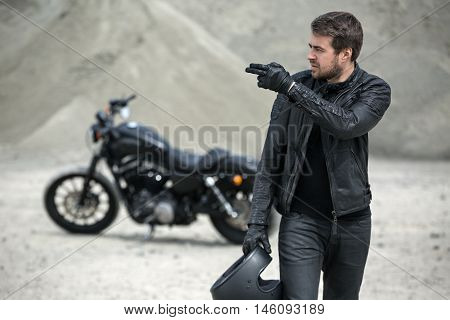 Brutal man stands in front of the black motorbike on the blurry background outdoors. He looks to the right and indicates two fingers of left hand to the right. In the right hand he holds a black helmet. He wears black jeans, a black T-shirt, black gloves,