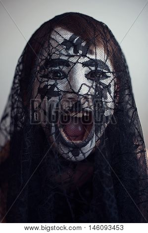Portrait of a spooky girl screaming behind the veil