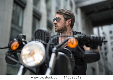 Charismatic man sits on the black motorbike on the skyscraper background. Headlamp switched on. He wears a black T-shirt, black gloves and sunglasses. He looks to the right with parted lips. He holds hands on the rudder.
