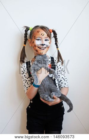 Sweet portrait of a happy little girl with face painted like a leopard holding a gray kitten
