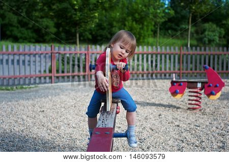 Little Girl Playing On A Teeter