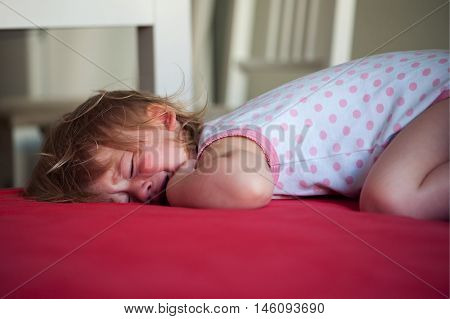 Sick baby girl lying in bed with a fever crying