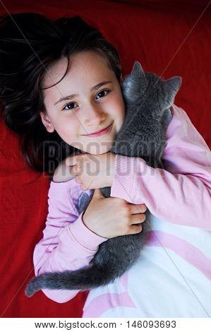 Happy little girl holding her gray kitten