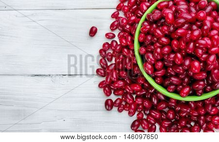 Green Full Plate Cornelian Cherries And Scattered Berry On The White Wood Board.selective Focus.top