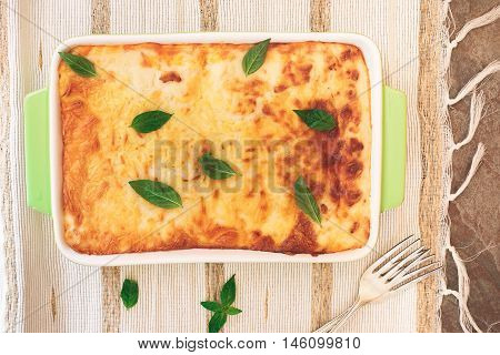 Lasagne in a baking dish. Top view, blank space