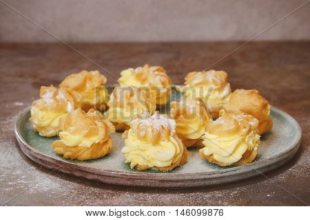 Cream puffs with cream filling and icing sugar, copy space