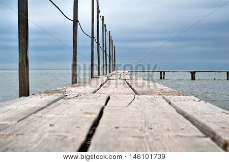 Wooden Laying On A Background Of Blue Sea. Boardwalk Pier On The Beach.