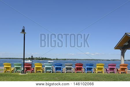A row of colorful Adirondack Chairs provide seating for vacationers in Clayton NY USA.