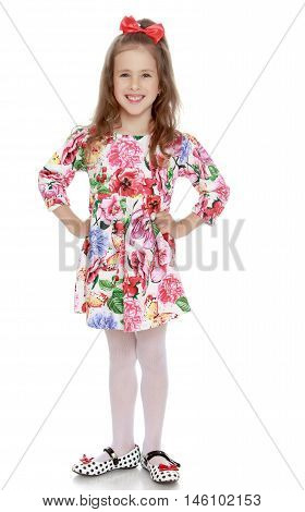 Laughing little girl with a long ponytail down to his shoulders, and a red bow on her head, in a beautiful summer dress. Full-length - Isolated on white background
