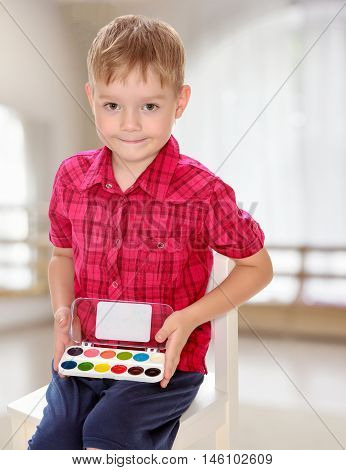 The concept of pre-school education of the child among their peers . in gaming room with a large arched window.Cute little boy in a red shirt holds his box of watercolors.