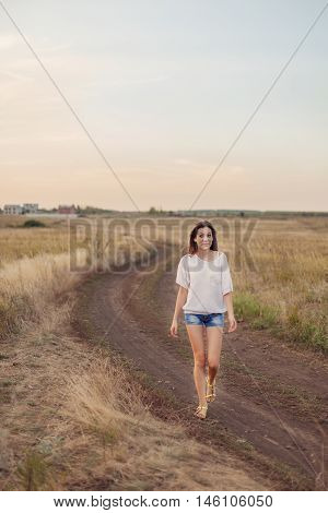 Young girl with long brown hair walking along the road in autumn field smiling and looks surprised. Selective focus warm tinted.