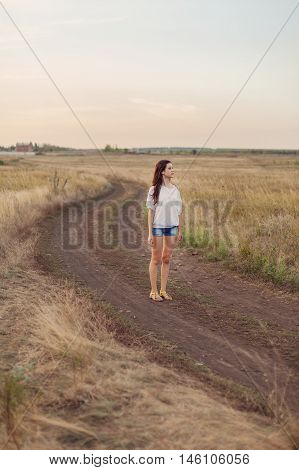 Young girl with long brown hair stays at the road in autumn field. Selective focus warm tinted.