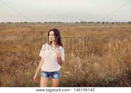 Young girl with long brown hair standing at the autumn meadow and looks thoughtfully left. Selective focus, warm tinted.