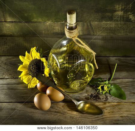 Sunflower oil in an old glass bottle with eggs and a spoon. On the wooden background with sunflowers