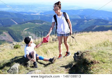 Summer adventure expedition in the mountains. Girl gives the boy a first aid kit.