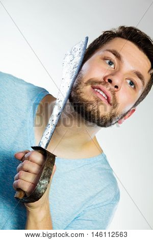 Handsome man bearded guy shaving with very large knife on gray background. Humour