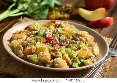 Quinoa Waldorf Salad with apple celery yellow raisins and walnut served on plate ingredients in the back photographed on dark wood with natural light (Selective Focus Focus in the middle of the salad)
