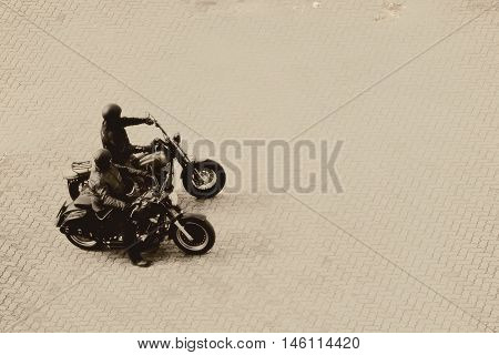 The aerial view of two motorbikes in the sunshine on a parking lot.