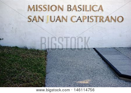 SAN JUAN CAPISTRANO, UNITED STATES - DECEMBER 25: The gold-trimmed nameplate of the Mission Basilica San Juan Capistrano on a white wall on December 25, 2015 in San Juan Capistrano.