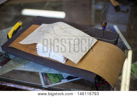 A bookbinder prepares to assemble a new journal.