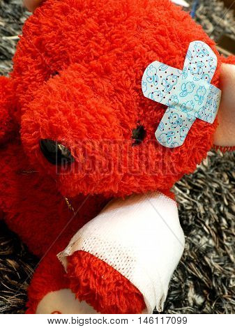 Red teddy bear with broken arm and bandage over his head.