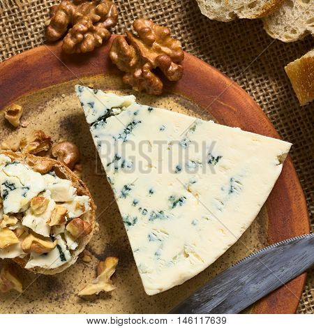 Blue cheese with blue cheese and walnut canape on plate photographed overhead with natural light (Selective Focus Focus on the top of the canape and the blue cheese slice)